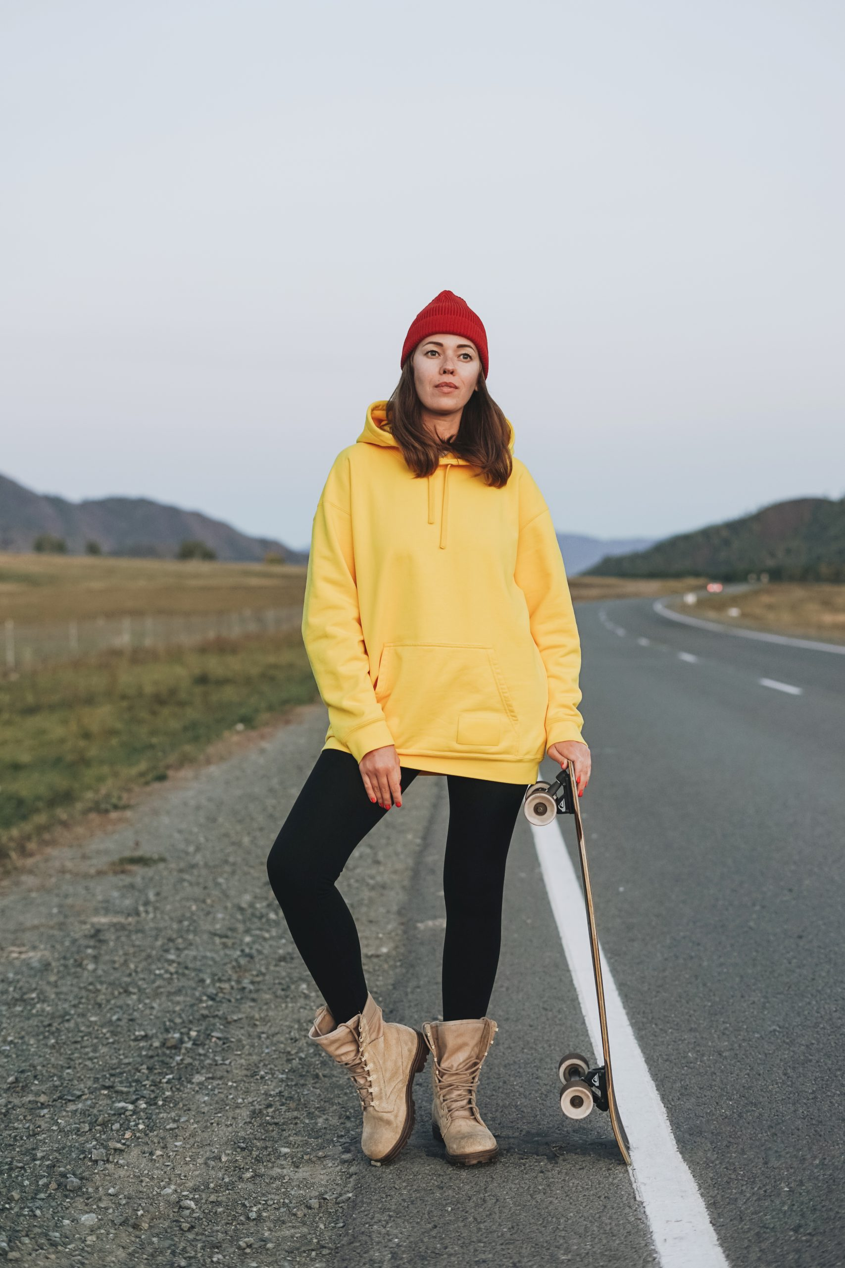 Young woman in yellow hoodie and red hat on skateboard on road against beautiful mountain landscape, Chuysky tract, Altai